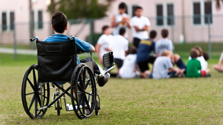 A boy using a wheelchair sits by himself and watches a team prepare for a game.