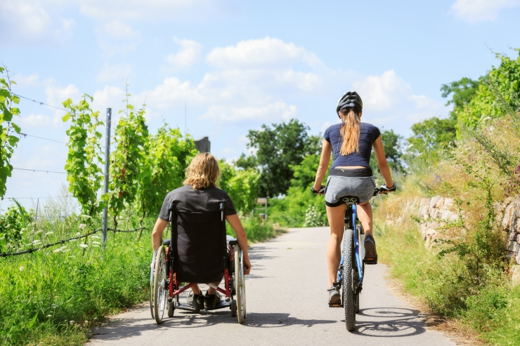 A man rolls in his wheelchair on the trail on the left while a woman cycles alongside him on the right.