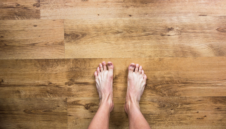 The top of a man's bare feet on a wood plank floor.