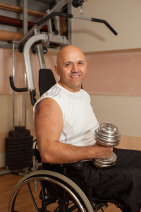 An image of a man using a wheelchair and holding a dumbbell.