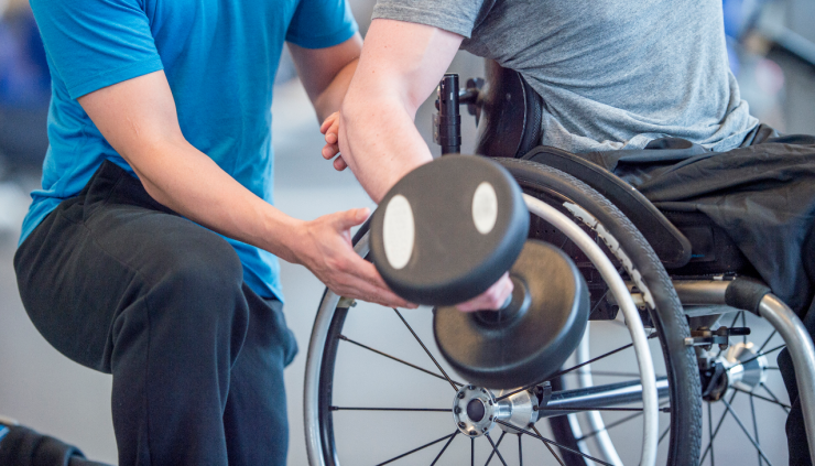 Man using a wheelchair doing a dumbbell curl with a spot from his trainer.