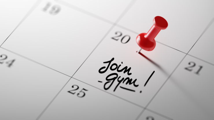 "Calendar with the text ""Join Gym"" written in script. A red push pin marks the date of the 20th."