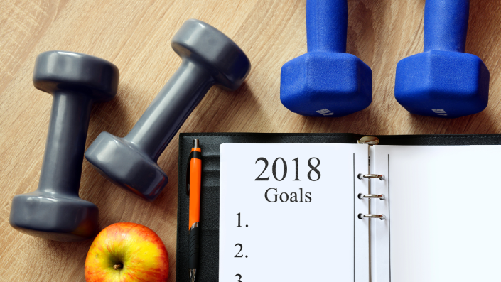 """Planner with the words """"2018 Goals"""" on the wood floor with dumbbells and an apple."""